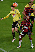 Michael McGlinchey (L) of the Phoenix jumps for the ball with West Sydney's Romeo Castelen during the A-League - Wellington Phoenix v Western Sydney football match at Westpac Stadium in Wellington on Sunday the 10 April 2016. Copyright Photo by Marty Melville / www.Photosport.nz