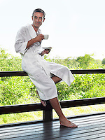 Adult man in bathrobe leaning on terrace railing holding cup