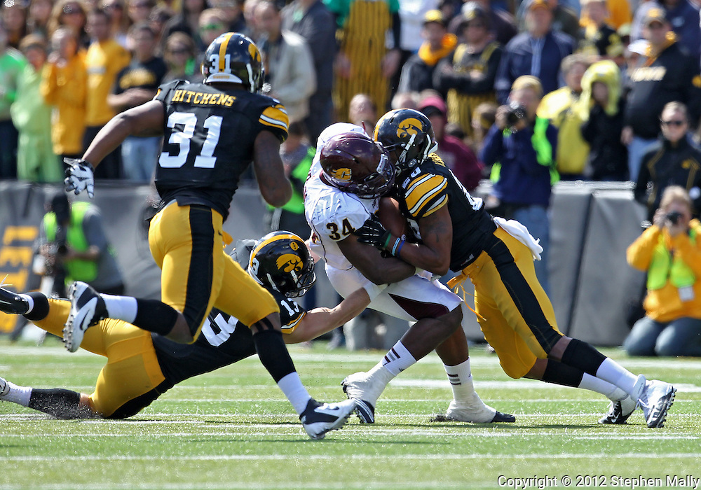 September 22 2012: Central Michigan Chippewas running back Zurlon Tipton (34) is hit by Iowa Hawkeyes linebacker Christian Kirksey (20) and linebacker Tom Donatell (13) during the second half of the NCAA football game between the Central Michigan Chippewas and the Iowa Hawkeyes at Kinnick Stadium in Iowa City, Iowa on Saturday September 22, 2012. Central Michigan defeated Iowa 32-31.