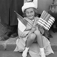 95146<br /> <br /> American President John Fitzgerald Kennedy (J.F.K.)'s visit to Ireland June 1963.<br /> Young girl (Margaret Murphy) seated at Dublin Airport with American flag and Irish flag, ready to welcome JFK on his historic visit.<br /> (Part of the Independent Newspapers Ireland/NLI collection.)