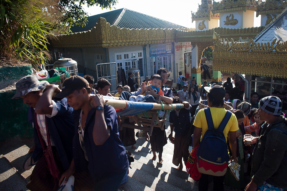 """A pair of pilgrims arrive to Kyaiktiyo Pagoda """"Golden Rock"""" in a kind of portable throne at Kyaiktiyo, Myanmar on Saturday, 1, Feb. 2014. That is one of the tourist attractions in the area."""