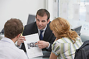 Couple observing brochure with real estate agent in office