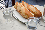 two halve baguettes with cheese and two glasses of water
