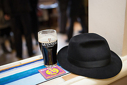 © Licensed to London News Pictures . 01/02/2014 . Manchester , UK . Nigel Farage's hat and pint of Guinness placed on a shelf in The Mountain Ash pub whilst he gives an interview to a journalist . Nigel Farage , the leader of the UK Independence Party ( UKIP ) joins candidate John Bickley on the campaign trail ahead of the Wythenshawe and Sale East by-election , following the death of MP Paul Goggins . Photo credit : Joel Goodman/LNP