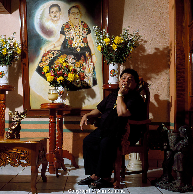 "Juchitan, Mexico: Although Oscar doesn't often dress as a woman, he started ""Las Intrepidas"", a muxe rights group, in Juchitan, Mexico.  He has let the younger generation take over especially since the death in 2008 of his mother, pictured here with his father in a painting in the living room which forms their altar. Muxes are very common, and accepted, in this Southern Oaxacan region, which claims to not discriminate against gays. The matriarchal society is still driven by women but in flux in the machismo culture of Mexico. (photo: Ann Summa)."