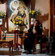 """Juchitan, Mexico: Although Oscar doesn't often dress as a woman, he started """"Las Intrepidas"""", a muxe rights group, in Juchitan, Mexico.  He has let the younger generation take over especially since the death in 2008 of his mother, pictured here with his father in a painting in the living room which forms their altar. Muxes are very common, and accepted, in this Southern Oaxacan region, which claims to not discriminate against gays. The matriarchal society is still driven by women but in flux in the machismo culture of Mexico. (photo: Ann Summa)."""