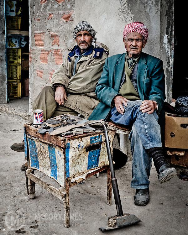 Tunisian men sitting in front of an old building in Jen Douba, Tunisia