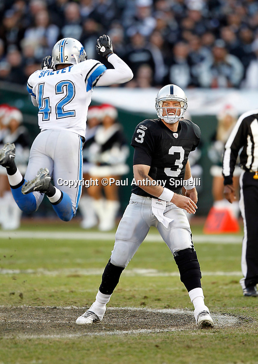 Oakland Raiders quarterback Carson Palmer (3) grimaces as he throws a pass under pressure from leaping Detroit Lions strong safety Amari Spievey (42) during the NFL week 15 football game against the Detroit Lions on Sunday, December 18, 2011 in Oakland, California. The Lions won the game 28-27. ©Paul Anthony Spinelli