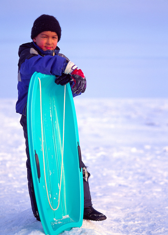 Alaska. Nome. Young eskimo boy sleds on sea ice in the Bering Sea.