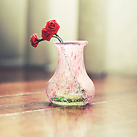 Close up of a decorated small pink pitcher with three red roses made of cloth inside.