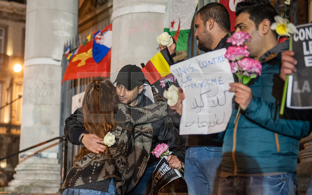 """© Licensed to London News Pictures. 23/03/2016. Brussels, Belgium. Late night vigil one day after the attacks - Place de la Bourse, a large crowd gather to light candles, sing and write messages in chalk on the paving stones of the square.  A group stand off to one side with placards reading """"We are together against terrorism""""and """"Counter terrorism and hate"""" and are embraced by a passer by. Photo credit: Guilhem Baker/LNP"""