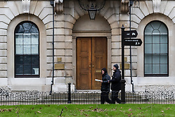 © Licensed to London News Pictures. London, UK. 30/12/2015. Two men carrying plates walk within the Royal Mint building courtyard. Squatters have occupied the former Royal Mint building, located opposite the Tower of London on the border of the City of London to protest against homelessness and highlight how empty buildings could provide shelter for rough sleepers. The site was previously used to manufacture British coins but is currently vacant and activists argue that this along with other vacant commercial buildings could be used to provide short term shelter for the homeless. Photo credit : Vickie Flores/LNP