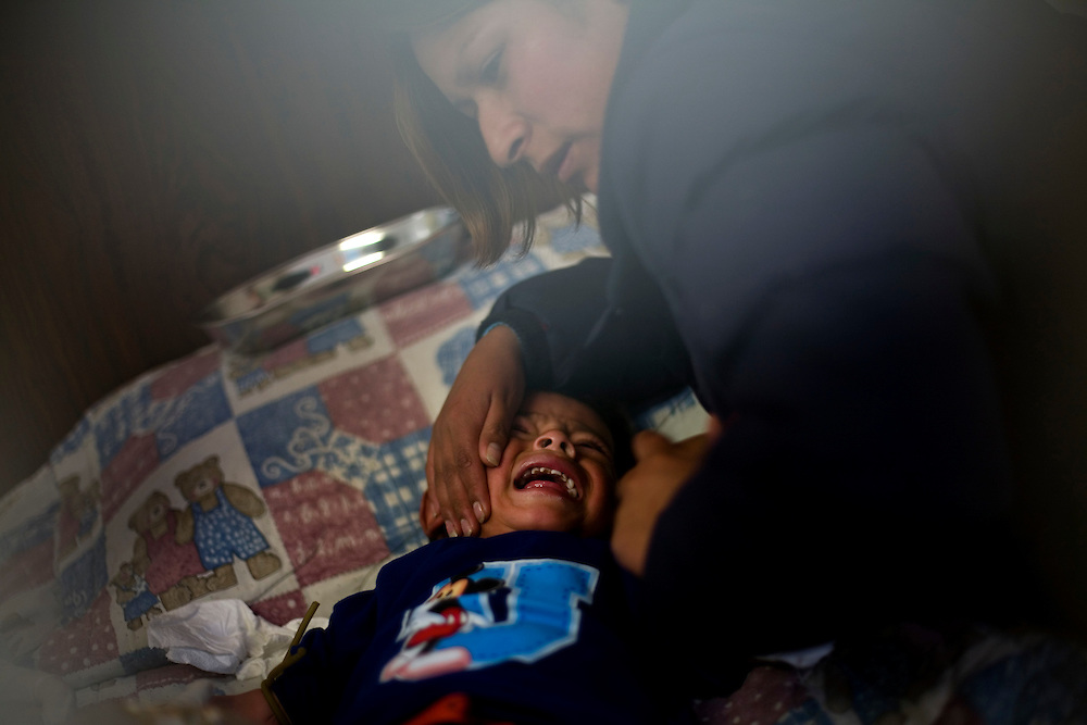 A mother calms her child as the Ministry of Health draws blood to test the level of lead in his blood. This was the last day of a month long of free testing for children 0-5.  Studies show that nearly 100% of the children living in La Oroya have lead poisoning, due to the proximity of a metal processing plant.