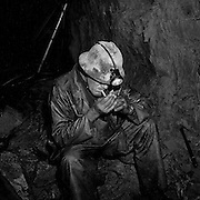 The late Lester Beattie smoking after drilling in a bypass drift, 1450 foot level Kerr Mine, Virginiatown, Ontario. From the book Cage Call: Life and Death in the Hard Rock Mining Belt. An in-depth project spanning over 12-years examining communities in one of the richest mining regions in the world located in Northwestern Ontario and Northeastern Quebec in Canada.