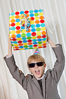 Happy boy wearing sunglasses holding gift aloft while shouting
