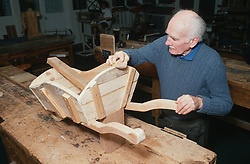 Male patient making wooden wheelbarrow during occupational therapy session,