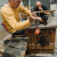 "VENICE, ITALY - DECEMBER 14:  Marino Santi, master ""maestro"" glass maker and assistant Stefano Costantini at Eugenio Ferri & C.  in Murano make glass Christmas baubles on December 14, 2010 in Venice, Italy. The production of glass baubles is an highly skilled process,with a variety of styles, often with the inclusion of gold and silver foil."