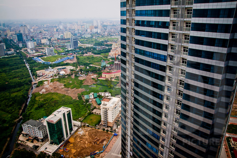 A newly-built, modern high-rise rises above a devloping area of the city, My Dinh, Hanoi, Vietnam