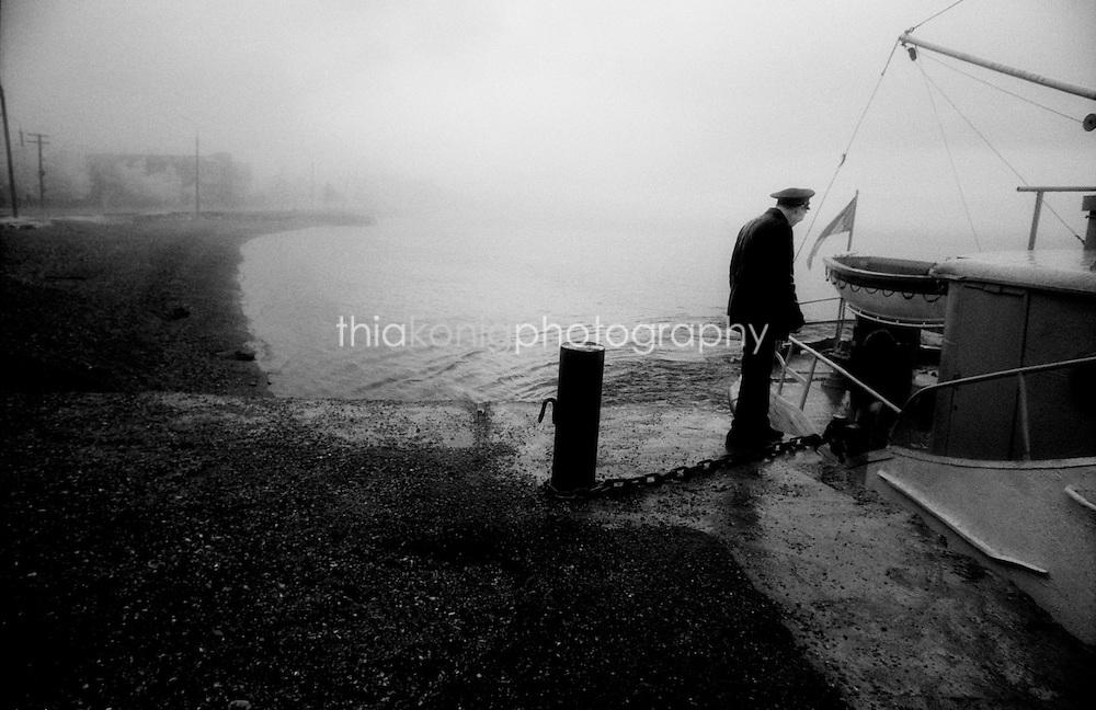 Captain of the Baikal ferry boat walks the gangplank on a gloomy day, Lake Baikal, Siberia