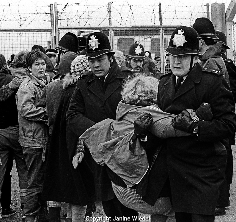 Police removing and arresting protesters at the anti-nuclear Greenham Common Women's Peace Camp in 1983 / 1984. The women only camp surrounded the RAF  base in Berkshire (UK) where American cruise missiles were being stored.
