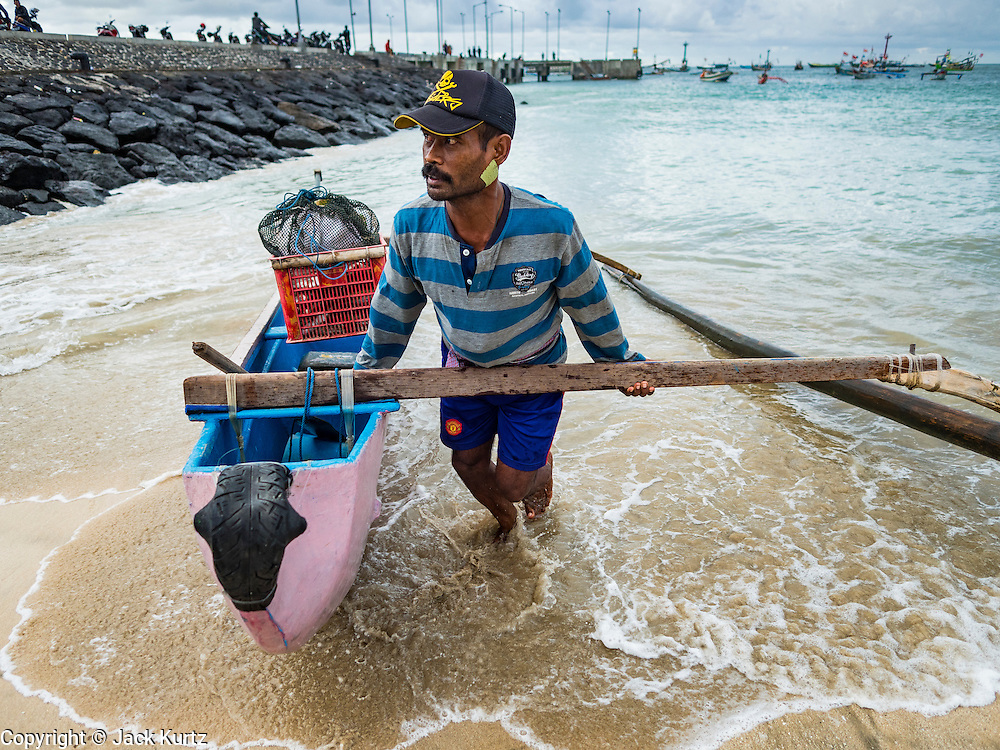 18 JULY 2016 - KUTA, BALI, INDONESIA:  A fisherman brings his small outrigger canoe into shore at Pasar Ikan pantai Kedonganan, a fishing pier and market in Kuta, Bali.   PHOTO BY JACK KURTZ