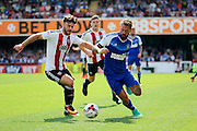 Ipswich defender and captain Luke Chambers (4) and Brentford forward Scott Hogan (9)  battle for the ball during the EFL Sky Bet Championship match between Brentford and Ipswich Town at Griffin Park, London, England on 13 August 2016. Photo by Matthew Redman.