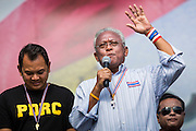 "09 MAY 2014 - BANGKOK, THAILAND: SUTHEP THAUGSUBAN (right) speaks from the main PDRC stage in Lumpini Park Friday. He went onto lead a march with thousands of anti-government protestors to Government House in the Dusit neighborhood of Bangkok. Thousands of Thai anti-government protestors took to the streets of Bangkok Friday to start their ""final push"" to bring the popularly elected of government of Yingluck Shinawatra. Yingluck has already been forced out by a recent court ruling that forced her to resign and she is facing indictment by the National Anti Corruption Commission of Thailand for alleged improprieties related to a government rice price support scheme. The protestors Friday were marching to demand that she not be allowed to return to politics. The courts have not banned her party, Pheu Thai, which has formed an interim caretaker government to govern until elections expected in July, 2014. Suthep Thaugsuban, secretary-general of the People's Democratic Reform Committee (PDRC),  said the president of the Supreme Court and the new senate speaker, who would be selected Friday, should set up an ""interim people's government and legislative assembly."" He went onto say that if they didn't, he would.     PHOTO BY JACK KURTZ"
