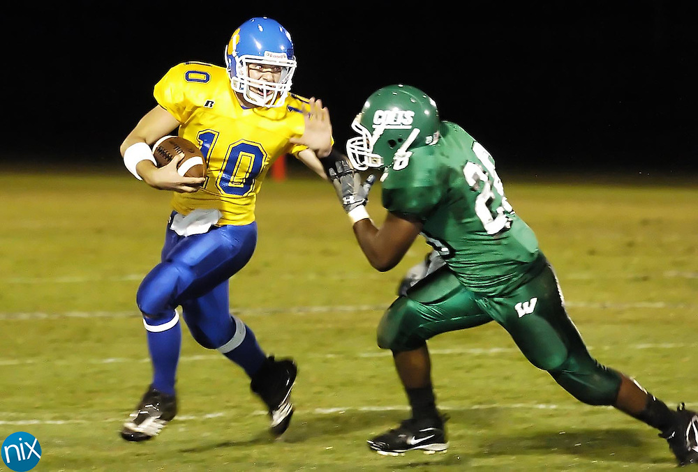 Mount Pleasant quarterback Tye Hill puts out a stiff arm on West Stanly's Damarquis Jackson Friday night in Oakboro.