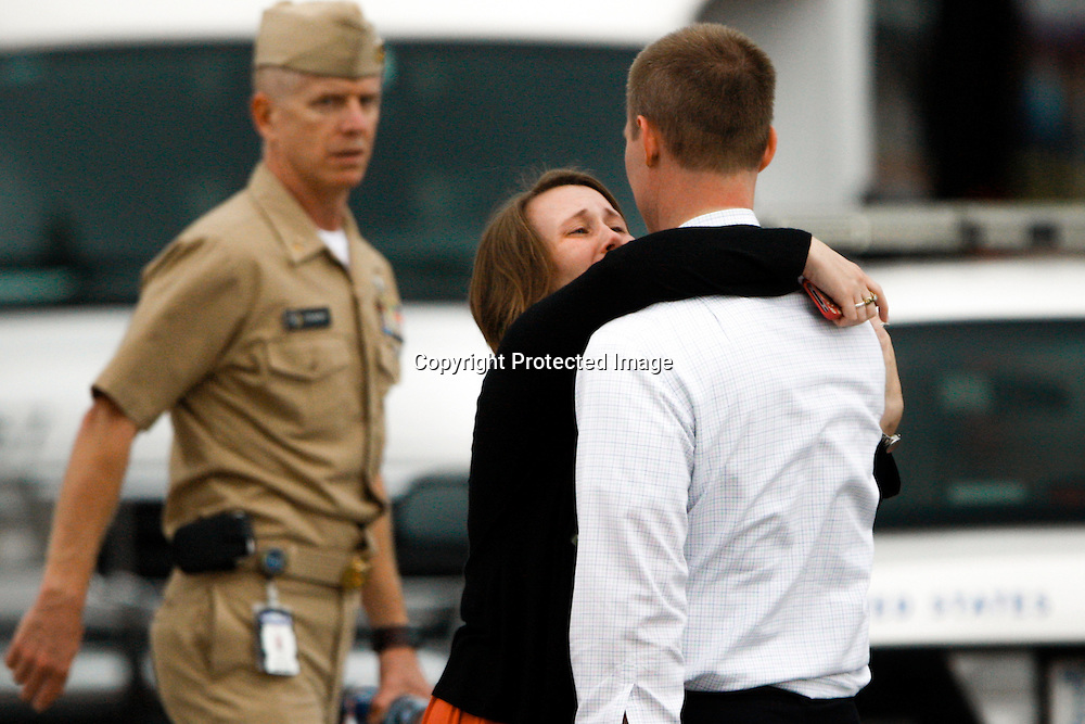A woman sobs as she and a loved one are reunited at the Red Cross rendezvous point for family members of employees who were working inside the Washington Navy Yard, where lone gunman Aaron Alexis fatally shot twelve people and injured three others in a mass shooting, in Washington.