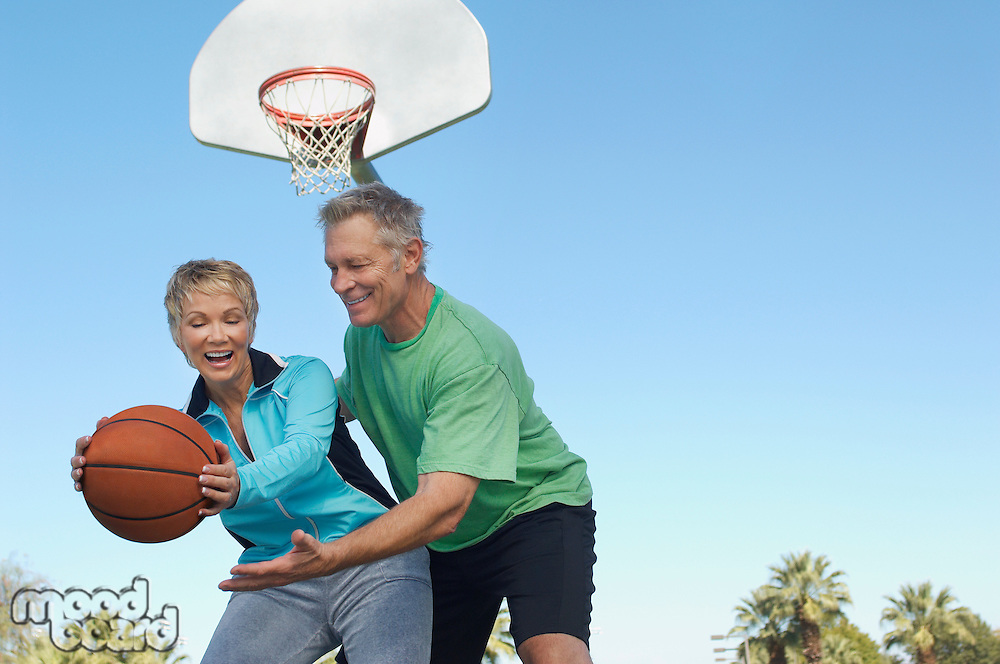 Senior couple playing basketball on outdoor court