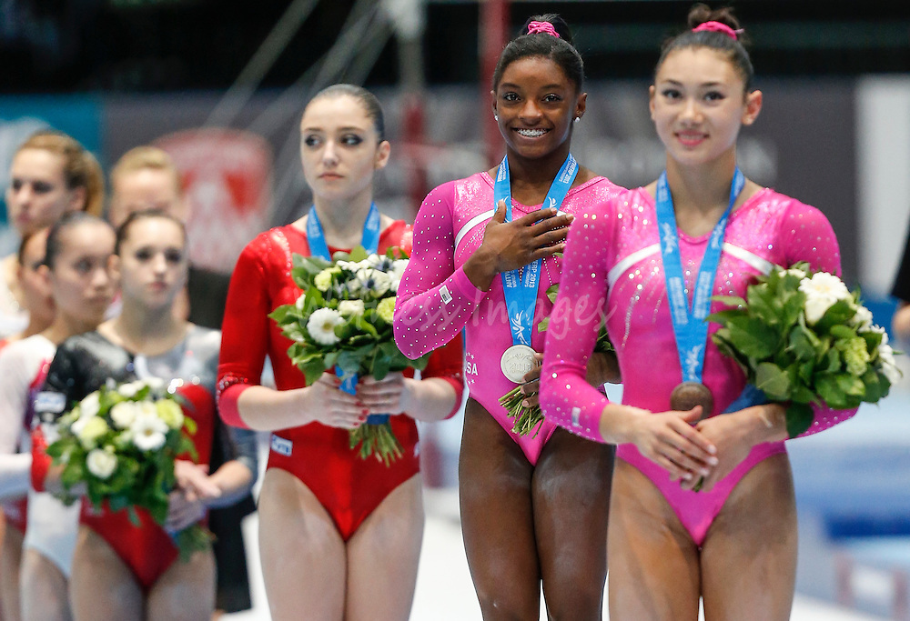 (from L-R) Bronze medalist Aliya Mustafina of Russia, gold winner Simones Biles of the U.S. and silver medalist Kyla Ross of the U.S. listen to national anthems during the women's all around final at the Artistic Gymnastics World Championships in Antwerp, Belgium, 04 October 2013.
