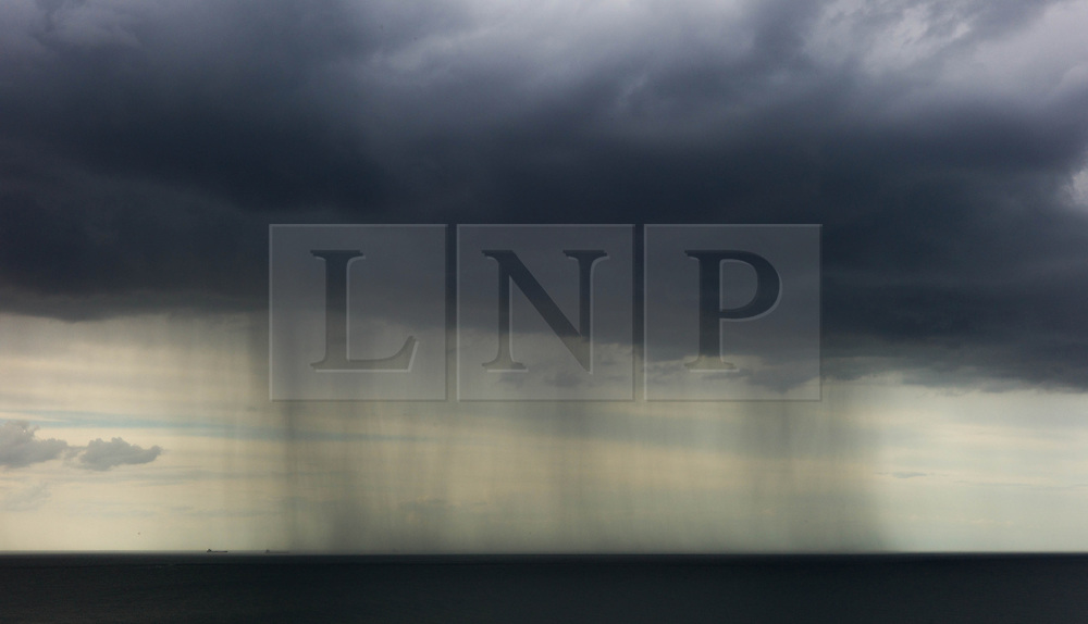 © Licensed to London News Pictures. <br /> 08/06/2014. <br /> <br /> Saltburn, United Kingdom<br /> <br /> Rain falls as dark and brooding thunder clouds form over Saltburn, Cleveland.<br /> <br /> Photo credit : Ian Forsyth/LNP
