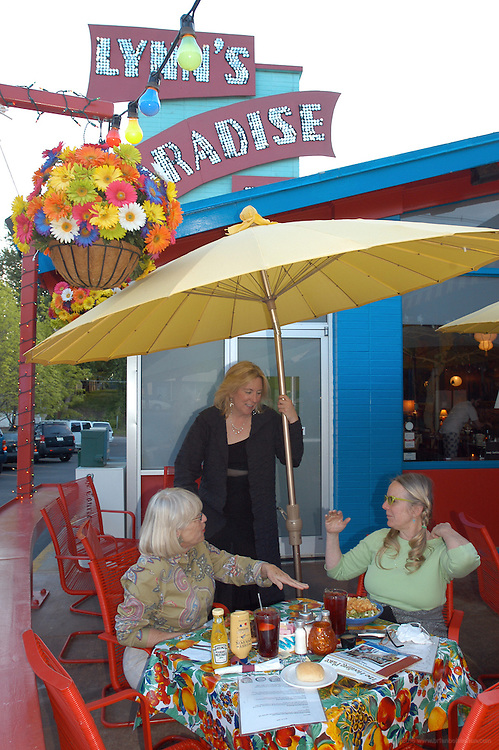 Lynn Winter, owner of Lynn's Paradise Cafe, center, talks with locals Nancy Seymour, left, and Deborah Keesee during dinner Tuesday, April 25, 2006, in Louisville, Ky...Photo by Brian  Bohannon , Freelance.