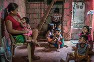 """Roda, 29 years old, and the 7 children for whom she is responsible, after her husband, Crisanto, a garbage picker at the massive dump site nearby, was killed in an extrajudicial killing as part of Duterte's """"War on Drug"""".  Roda cannot work because she has a ulcerous infection on her thigh and she also needs to look after the children.  Some of the older children are sent out to sell fried banana and other food on the street to bring in a little cash.  Payatas, Metro Manila, Philippines."""