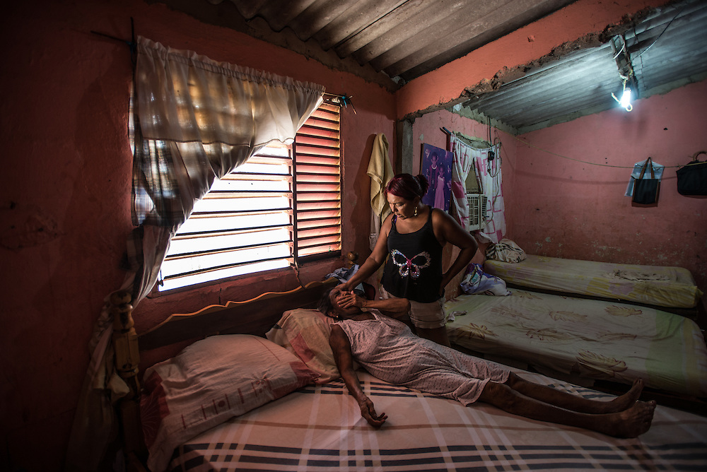 "LA VELA, VENEZUELA - SEPTEMBER 11, 2016: Maria Piñero takes care of her elderly mother, Felipa Palencia de Piñero, who is diabetic. The family struggles to find the medicine that she needs. To escape the crisis, Ms. Piñero spent all of her savings to pay smugglers to take her in a small fishing boat to Curacao island. ""I'm nervous,"" she said. ""I'm leaving with nothing. But I have to do this. Otherwise, we will just die here hungry."" Another benefit of living and working in Curacao, she said, is that she will be able to find and pay for her mother's medicines, and ship them to her in Venezuela.  Despite having the largest known oil reserves in the world, Venezuela is suffering from hyperinflation and a severe economic crisis making affordable food difficult for most middle and working class families to access.  Well over 150,000 Venezuelans have fled the country in the last year alone, the highest in more than a decade, according to scholars studying the exodus. As Hugo Chávez's Socialist-inspired revolution collapses into economic ruin, as food and medicine slip further out of reach, the new migrants include the same impoverished people that Venezuela's policies were supposed to help. ""We have seen a great acceleration,"" said Tomás Paez, a professor who studies immigration at the Central University of Venezuela. He says that as many as 200,000 Venezuelans have left in the last year, driven by how much harder it is to get food, work and medicine — not to mention the crime such scarcities have fueled.  PHOTO: Meridith Kohut for The New York Times"