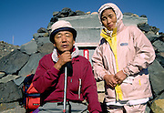 Portrait of two elderly climbers on the summit of  Mount Fuji, at 3,776 metres, the highest peak in Japan. Yamanashi Prefecture, Japan August 2005