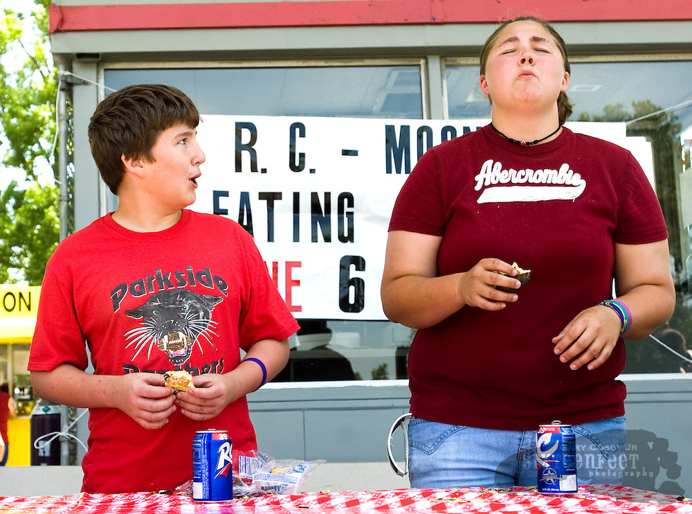 Photo by Gary Cosby Jr.  Four contestants battled for the crown in the Moon Pie eating contest Saturday in Morgan City.  The competition was part of the Morgan City Founder's Day Celebration. Justin Smithson watches Morgan Cothren as she struggles to get down her fifth pie.  Cothren won the event.