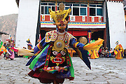November 2006 - Hongpo, China - A Tibetan Buddhist monk dressed in elaborate costume dances around the courtyard of the monastery. Every year the local monastery of this village celebrates an elaborate three-day Cham (Mask) dance where the monks will dress up in various costumes representing spirits in Tibetan Buddhism.<br /> Photo credit: Luke Duggleby