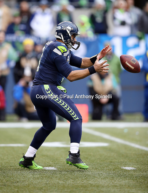 Seattle Seahawks quarterback Russell Wilson (3) catches a shotgun snap during the NFL week 20 NFC Championship football game against the Green Bay Packers on Sunday, Jan. 18, 2015 in Seattle. The Seahawks won the game 28-22 in overtime. ©Paul Anthony Spinelli
