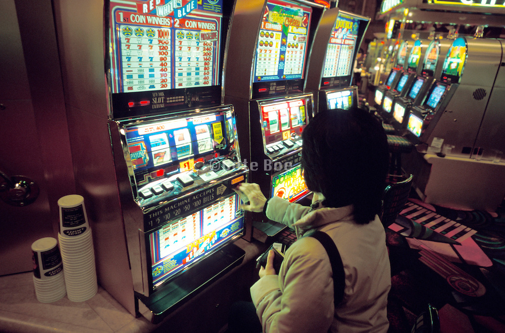 Woman putting money in a slot machine