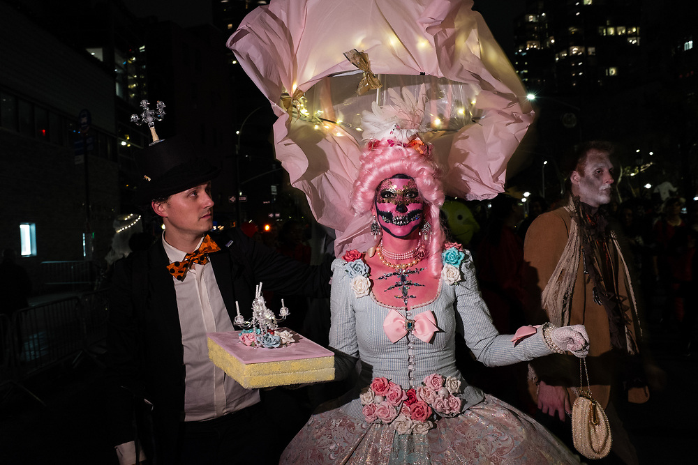 New York, NY - 31 October 2019. the annual Greenwich Village Halloween Parade along Manhattan's 6th Avenue. A woman in an elaborate dress with panniers wears a pink wigm elaborate headgear and a mask with jeweled death's head.