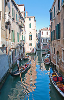 A busy canal with moored and working gondolas in Venice, Italy.