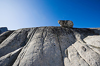 A rock sitting atop a grooved cliff wall, Enchantment Lakes Wilderness Area, Washington Cascades, USA.