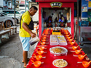 25 AUGUST 2018 - GEORGE TOWN, PENANG, MALAYSIA: A man sets up banquet for the spirits in front of a small neighborhood shrine on Ghost Day, the full moon day (or night) that falls in the middle of Hungry Ghost month. The Ghost Festival, also known as the Hungry Ghost Festival is a traditional Taoist and Buddhist festival held in Chinese communities throughout Asia. Ghost Day, is on the 15th night of the seventh month (25 August in 2018). During Ghost Festival, the deceased are believed to visit the living. In many Chinese communities, there are Chinese operas and puppet shows and elaborate banquets are staged to appease the ghosts.      PHOTO BY JACK KURTZ