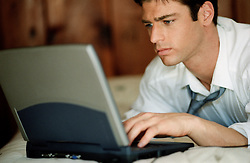 Man indoors with shirt and tie working on a laptop computer