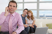 Real estate agent using mobile phone with couple in new home