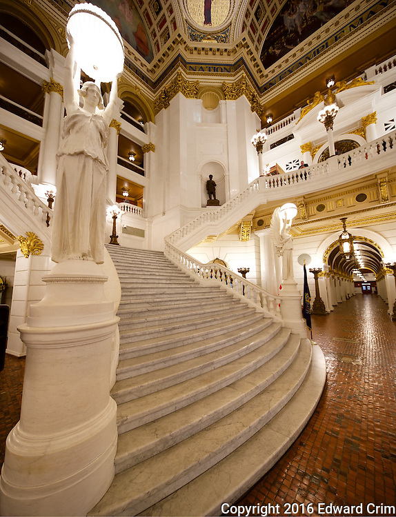 """View of the rotunda from the bottom of the grand stair in the Pennsylvania capitol in Harrisburg, showing the """"Angels of Light"""" on the north and south sides of the stair."""