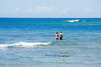 Tourists standing on the coral reef while snorkeling at Haena State Beach Park, Kauai, Hawaii, USA