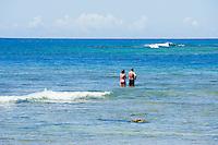 Tourists standing on the coral reef while snorkeling at Haena State Beach Park, Kauai, Hawaii, USA
