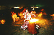 """Nightime celebrations with a mixture of prayers, flamenco singing, dancing around camp fires. The pilgrim route of the Hermandade de Sanlucar de Barrameda from Sanlucar across the Parque Donana to El Rocio, Huelva Province, Andalusia, Spain...El Rocio follows on from Semana Santa - Easter week and the various spring ferias, of which Seville's Feria de Abril (April) is the biggest. The processions to the (Hermitage) Hermita de El Rocío, at Pentecost, is the most famous (Romeria) pilgrimage in the Andalusian region, attracting nearly a million people from across Andalusia, Spain and the world. The cult started off in the 13th century when a statue of the virgin Mary was apparently found in a tree trunk in the Donana Park. What was first a local devotion at Pentecost by local pilgrim brotherhoods """"hermandades"""" became by the 19th century into dozens of fraternities developed from such as Cadiz, Selville and Huelva. Some walk for several days, others travel with oxen drawn wagons or on horseback, with traction engines and all terrain vehicles, camping along the trail they take. They wear Andalusian costumes, tight breeches, boots, short jackets and frilly flamenco skirts. Many festivities, flamenco dance, laments, songs and music are combined with religious prayers. Devout pilgrims walk as a penance, keeping vows of silence. An emblem of the immaculate conception (sin peche) is carried. On the Pentecost after the stroke of midnight on the whit Sunday the virgin Mary is carried from the church through the streets of El Rocio by each hermandade to visit each brotherhood's shrine."""